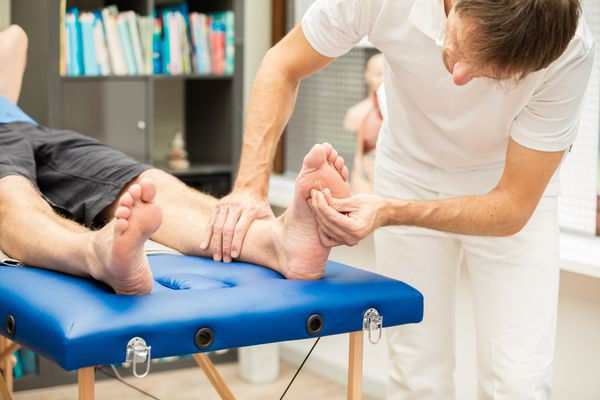 Doctor testing sensibility of foot