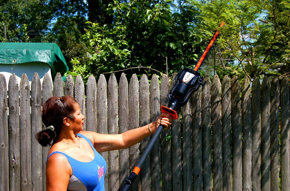 Woman trimming tree branches with the Remington Axcess Trimmer.