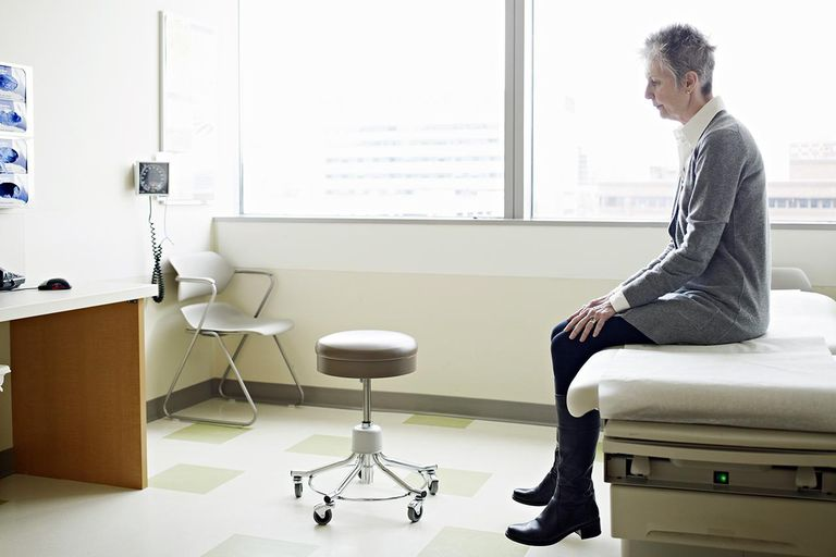 Mature female patient sitting on exam table in exam room looking down
