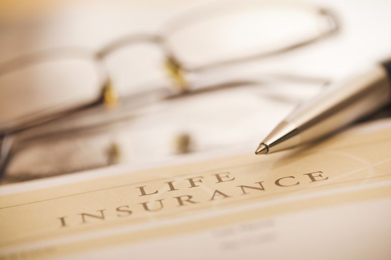 Life insurance policy with gold pen and eyeglasses