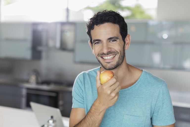 Man with apple eats a good diet.
