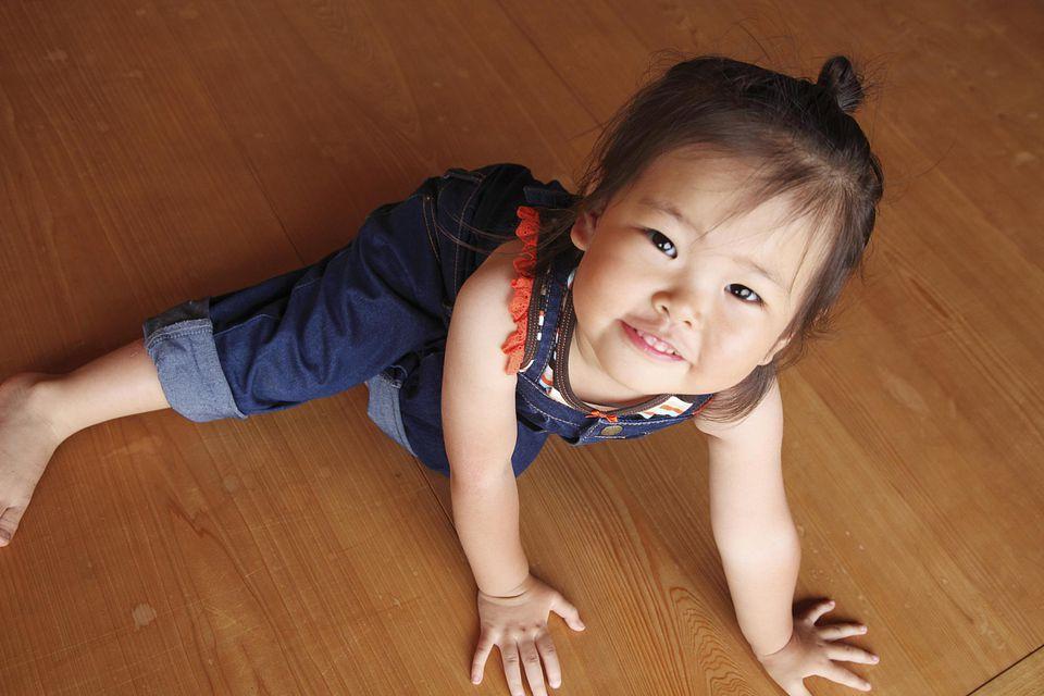 Little girl playing on a kid-friendly hardwood flooring