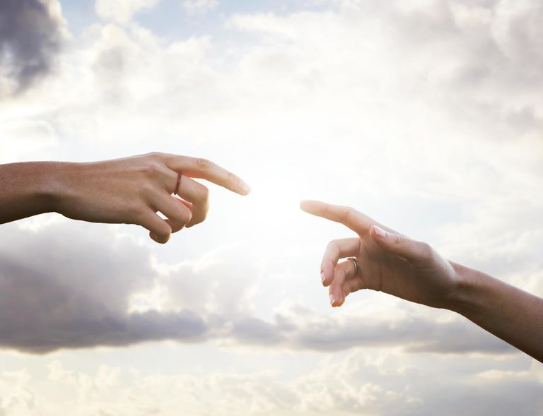 Close up of two hands connecting with sun.
