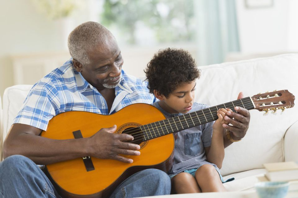 Boy playing guitar with grandfather