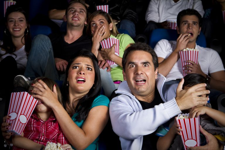 Image of people watching a movie with a scary or inappropriate scene