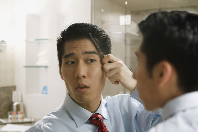 Korean businessman combing hair