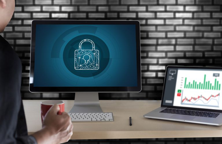 Person looking at a computer screens showing a lock to indicate antivirus protection.