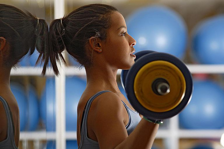 Young woman lifting weights, side view