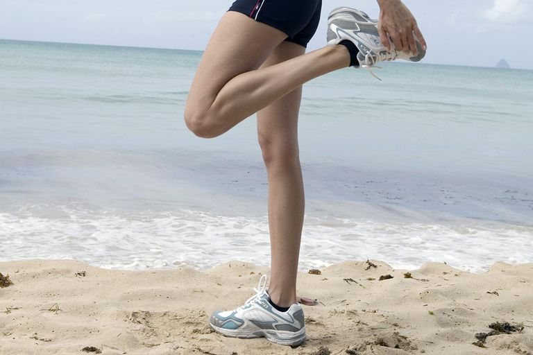 Young woman stretching calf muscle on beach, side view