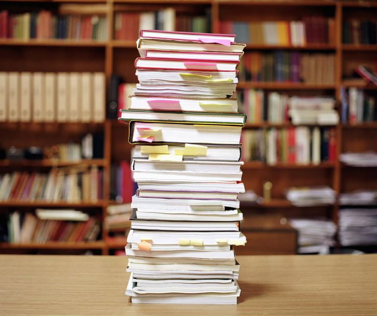 Pile of books on desk, sticky notes marking pages