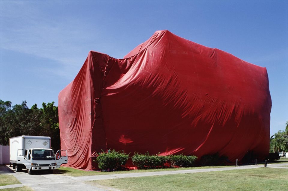 Exterminator van by building undergoing tent fumigation