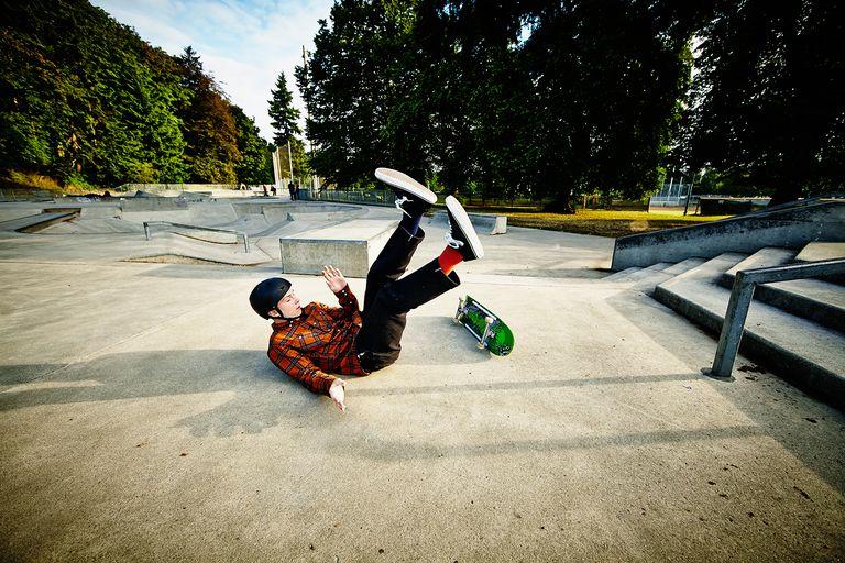 Skateboarder falling off of railing in skate park