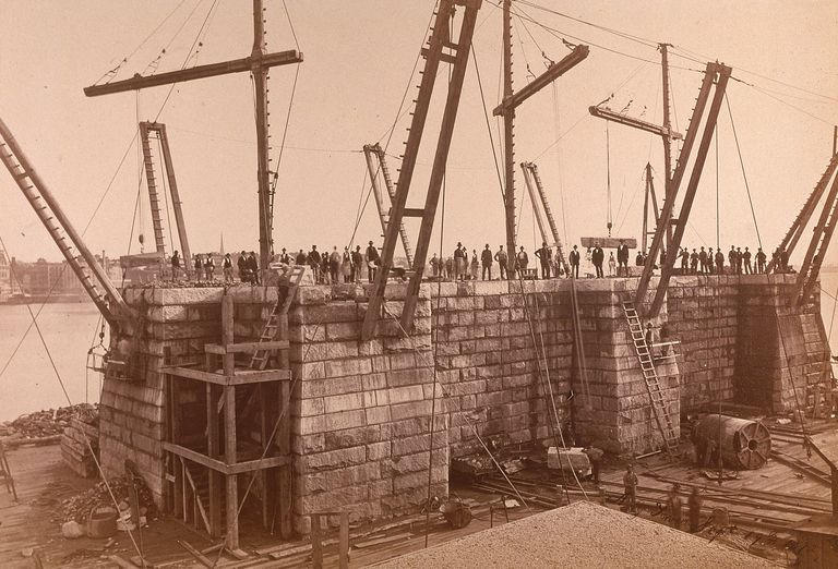 Photograph of a Brooklyn Bridge tower under construction.