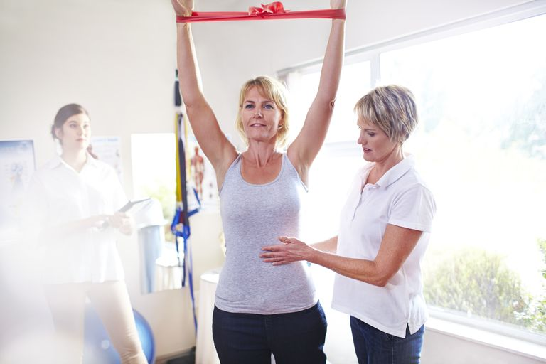 Physical therapist guiding woman pulling resistance band overhead