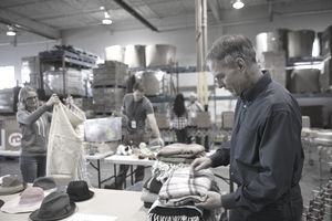 Male volunteer sorting clothing for clothing drive in warehouse