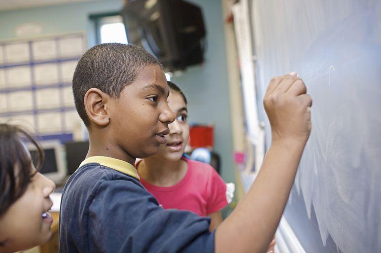 Children in school writing on blackboard