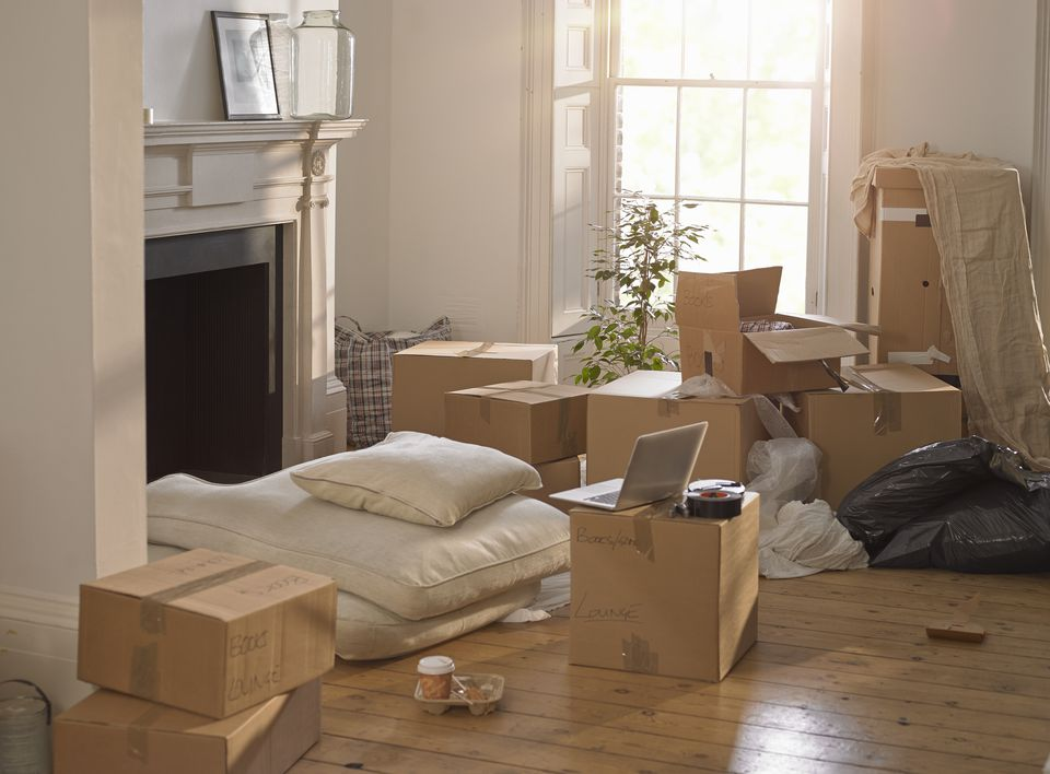 A room full of packing boxes and a laptop