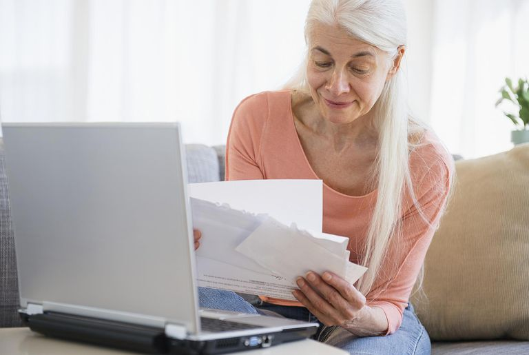Senior woman going over bills with laptop