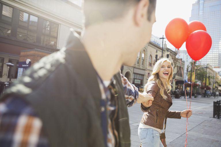 Smiling woman leading man down city street