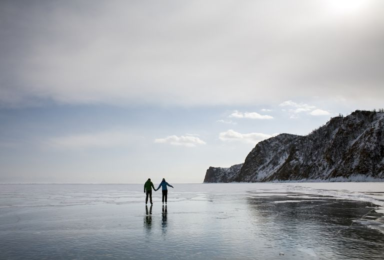 A couple ice skating on a frozen lake