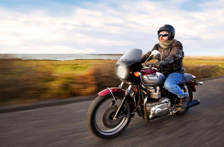 Bearded biker riding motorcycle next to ocean
