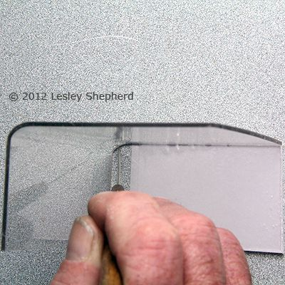 Scribing the corner on the side of a miniature display cabinet to match the cabinet front.