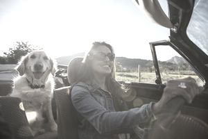 Mature woman and dog, in convertible car