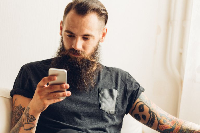 Tattooed man on cell phone