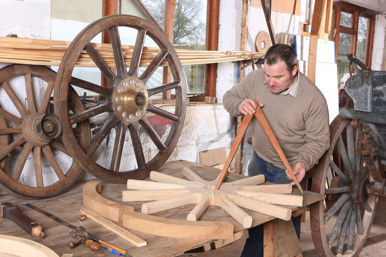 A wheelwright is someone who builds and/or repairs wagon wheels, carriages, etc. for a living.