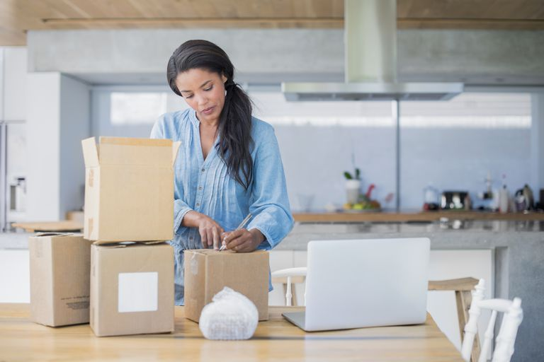 woman packing cardboard boxes for shipping