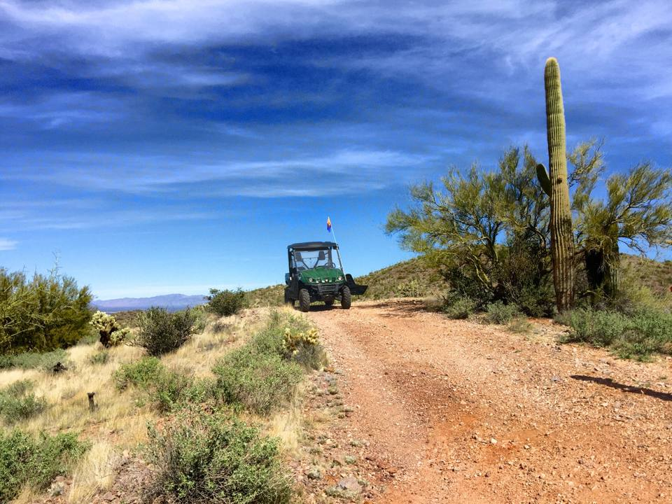 Off-Road Vehicle On Dirt Road Against Blue Sky