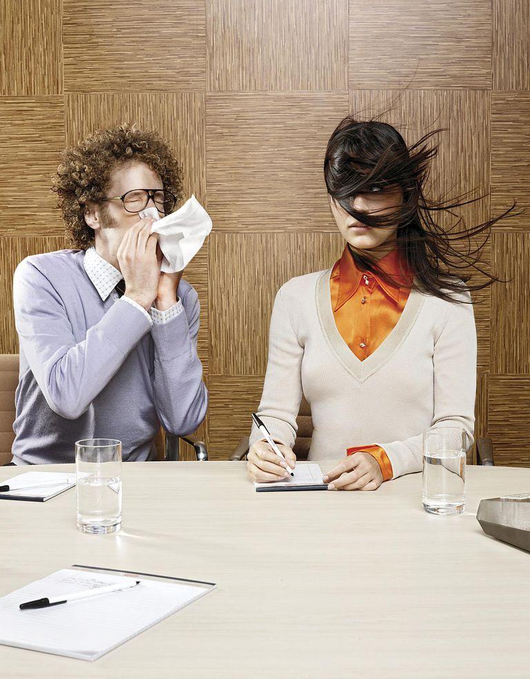 man sneezing toward woman
