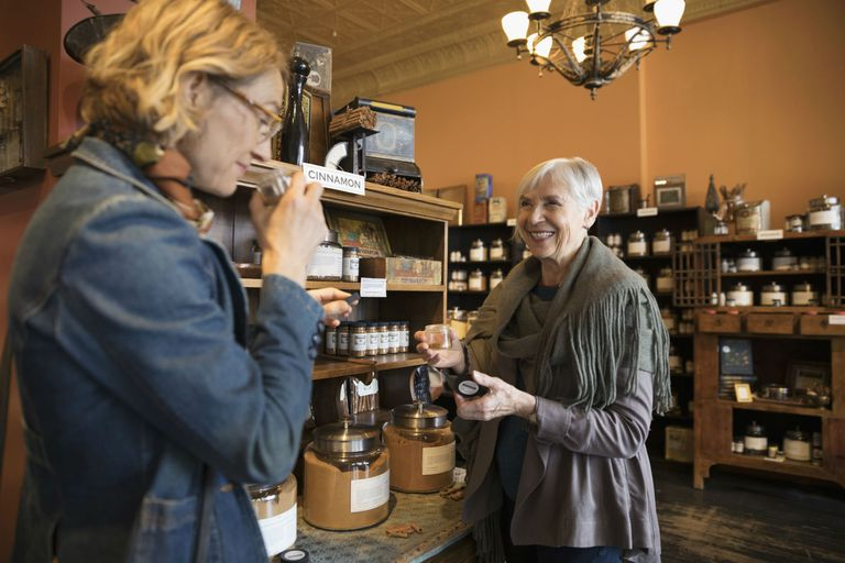 Mother and daughter smelling and shopping for spices in shop