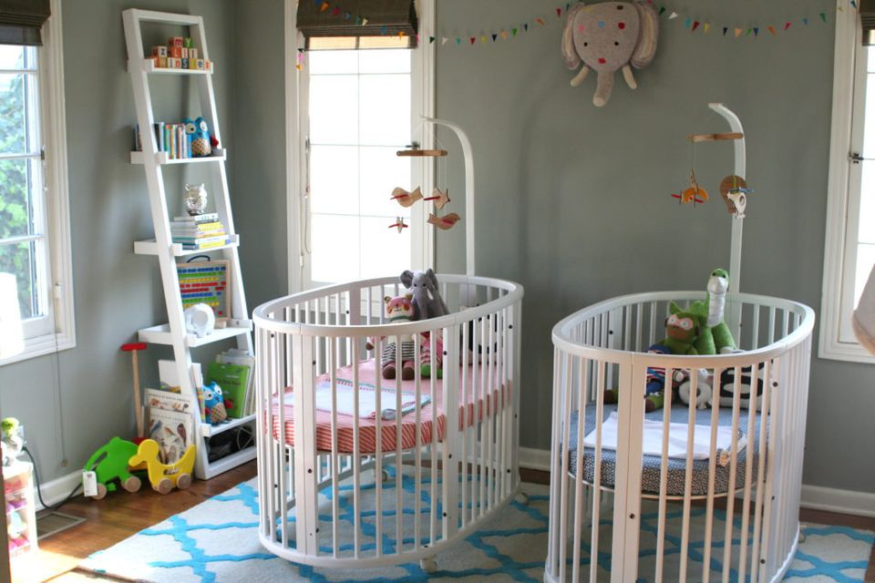 Simple twin nursery with a matching set of Stokke Cribs
