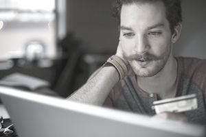Mustachioed man making online credit card purchase