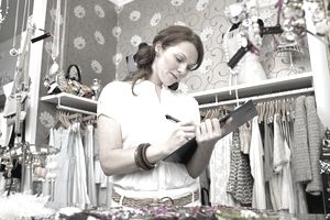 Young woman in clothes shop, holding clipboard and writing, low angle view
