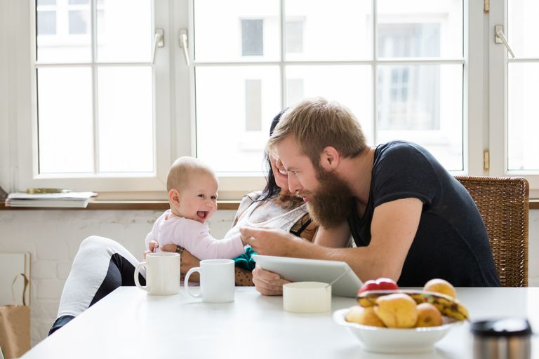young couple with baby sitting at table