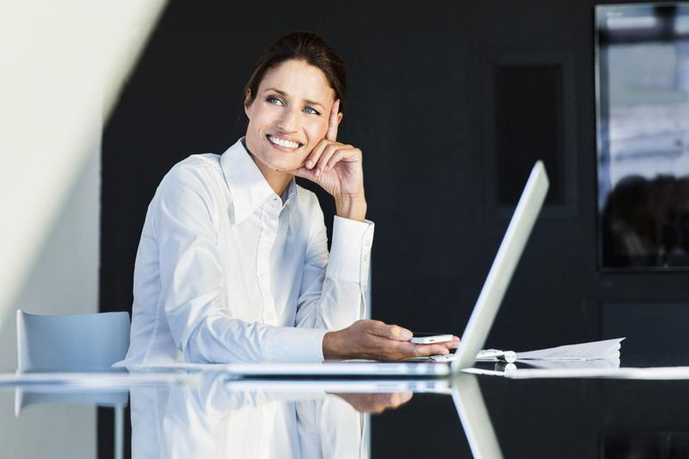Business woman working on a computer looking at a coworker.