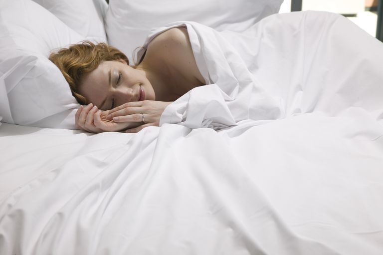 Young woman lying in bed, smiling, side view, close-up