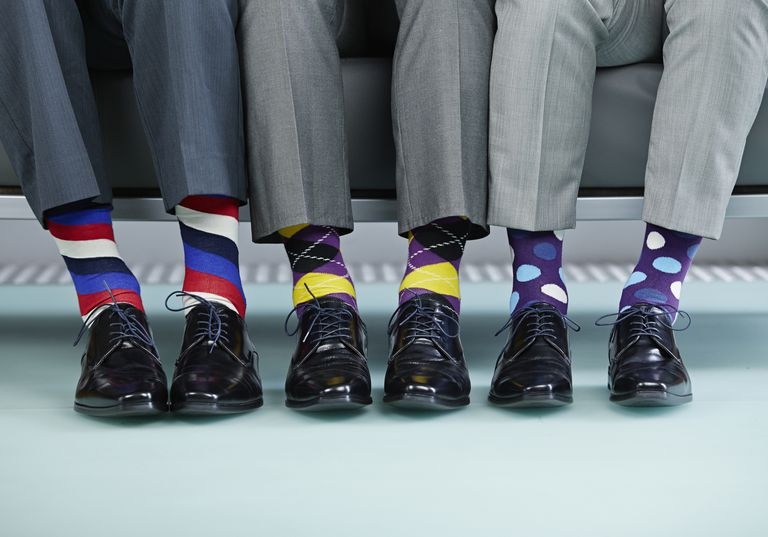 Men sitting on bench wearing colourful socks