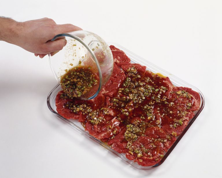 Man pouring marinade over Korean beef in heatproof dish prior to grilling