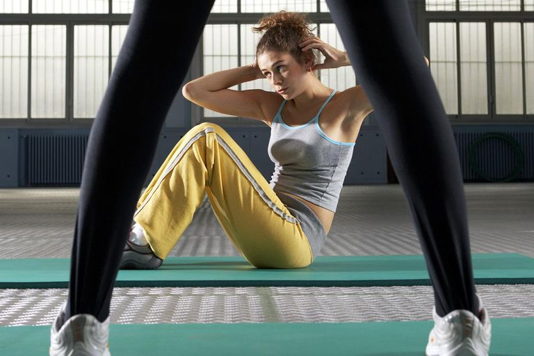 Exercise instructor standing by young woman performing situps