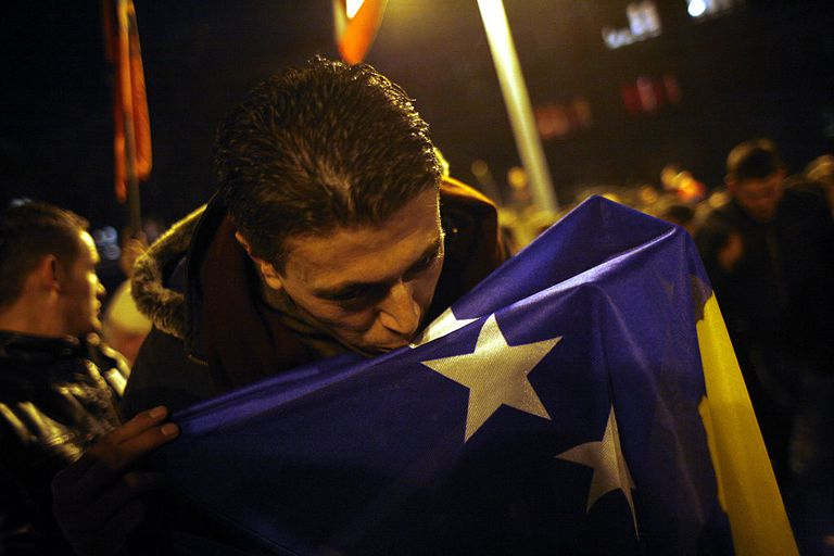 man kisses flag in celebration of Kosovo independence