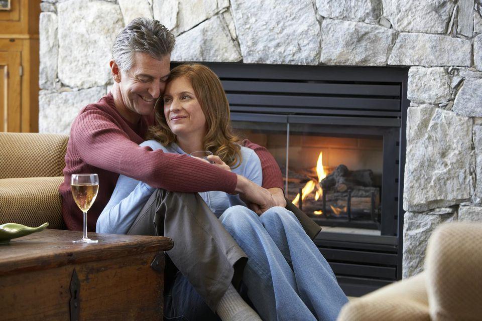 Mature couple sitting near fireplace, embracing, drinking wine