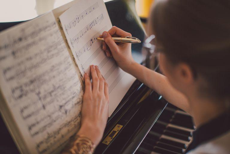 Woman writing sheet music at the piano