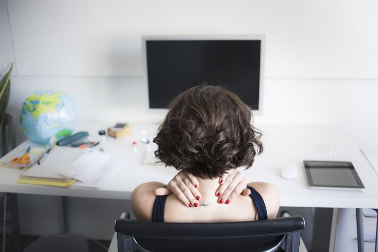 Young woman massaging her neck at desk