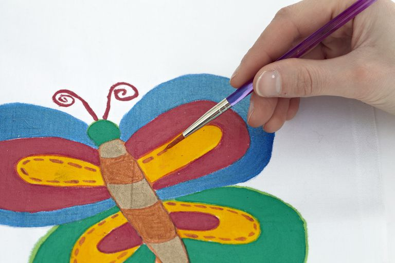 Painting butterfly on fabric, close-up