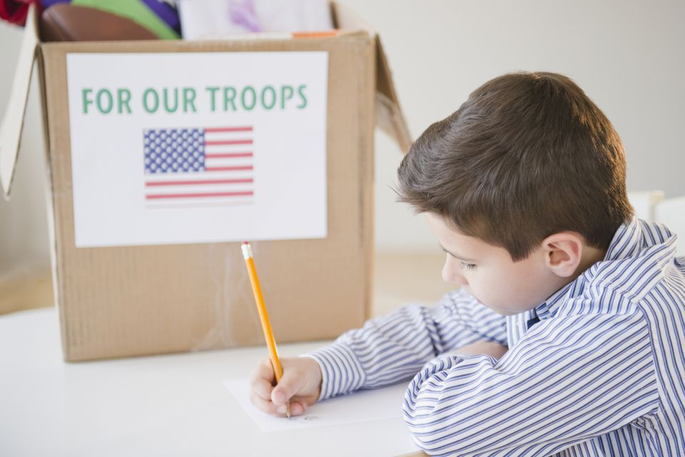 Young boy preparing care package for US Troops