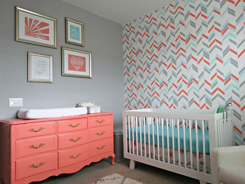 Grey and coral nursery with dramatic, chevron accent wall