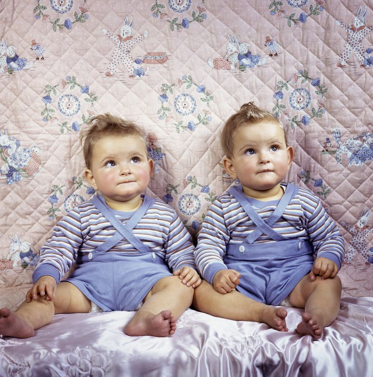 Twin babies dressed the same looking up